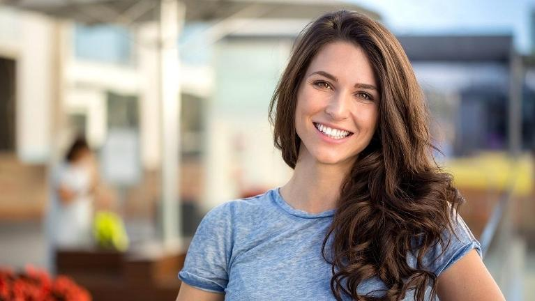 woman smiling after using invisalign to straighten teeth